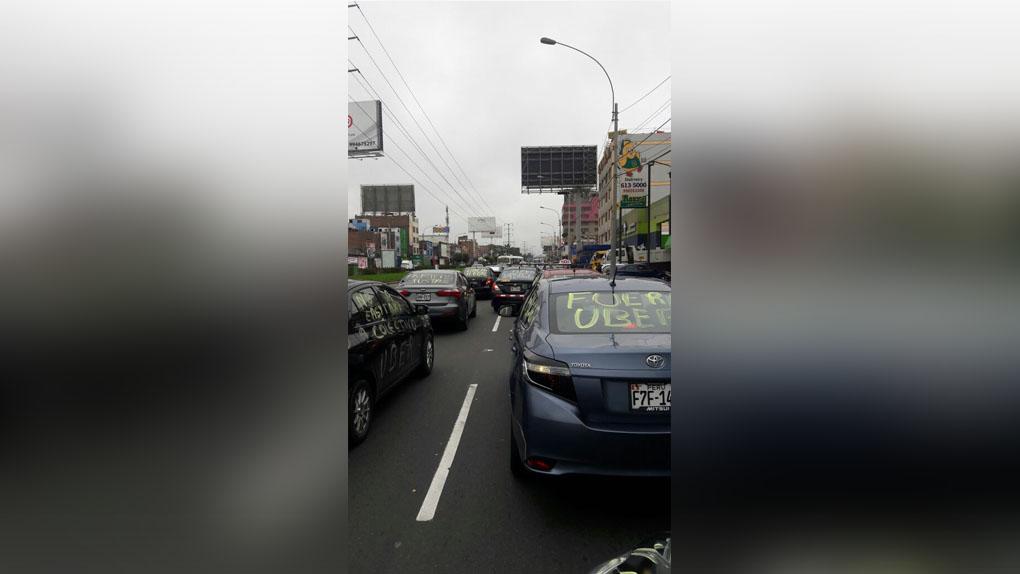 Autos en fila pintados con frases en contra de la empresa Uber generaron gran congestión vehicular en la avenida Pershing.