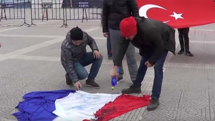 Momento en que ciudadanos turcos prenden fuego a bandera francesa.