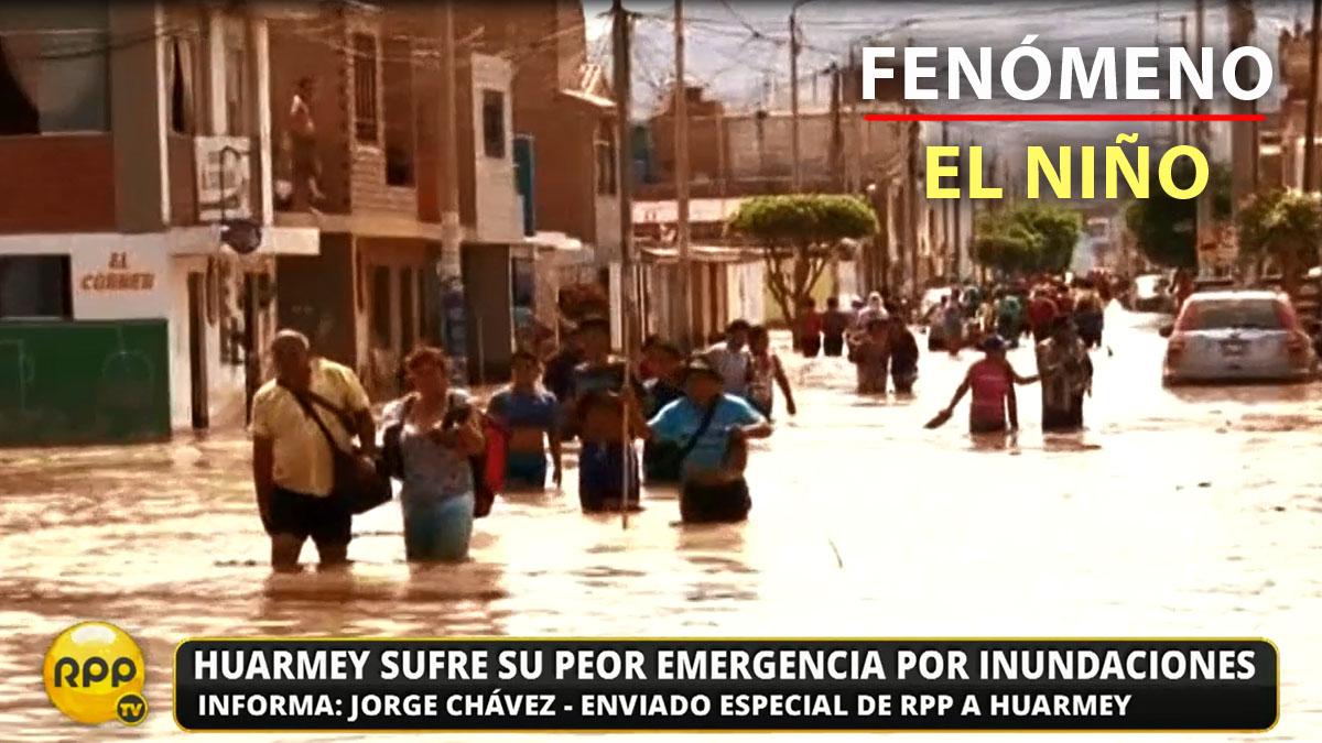 Las personas caminan sumergidos en agua en una calle de Huarmey.