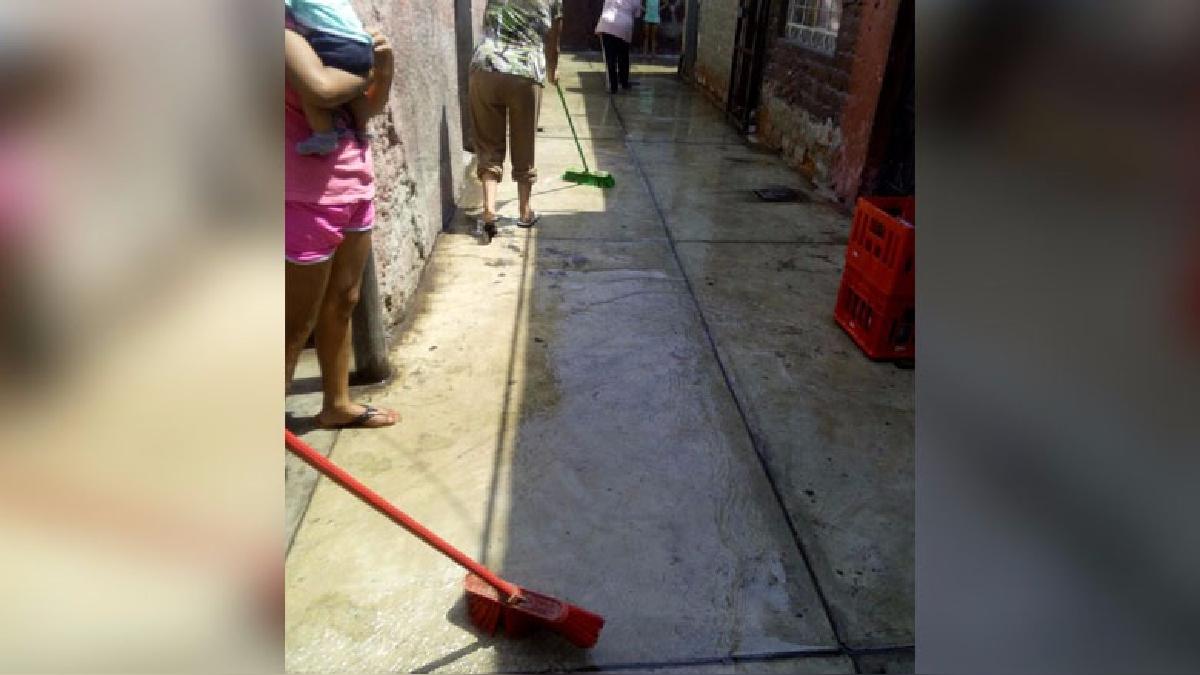 Con escobas en mano, desde hace tres días, vecinos de la quinta disminuyen la cantidad de agua empozadas en los pasillos.
