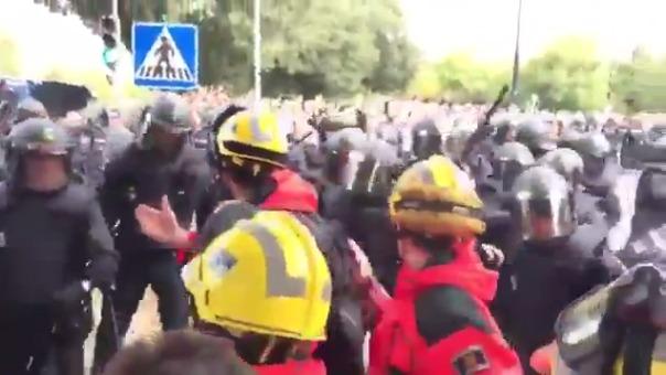 La Policía española ataca a bomberos que intentan proteger a los votantes.