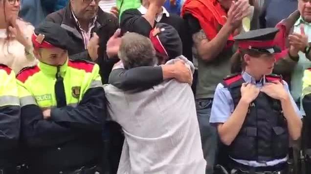 Los Mozos de Escuadra (Policía de Cataluña) y catalanes en un emotivo momento.