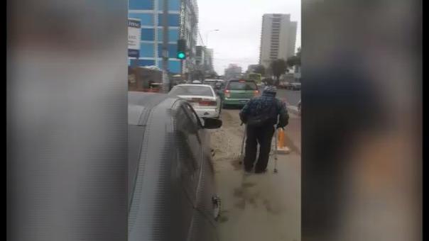 Incluso se aprecia cómo un señor con muletas tiene dificultad  para cruzar esta avenida debido a la cantidad de autos y motos estacionadas.