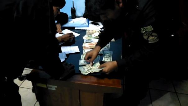 La Policía cuenta el dinero que se le incautó a los asaltantes.