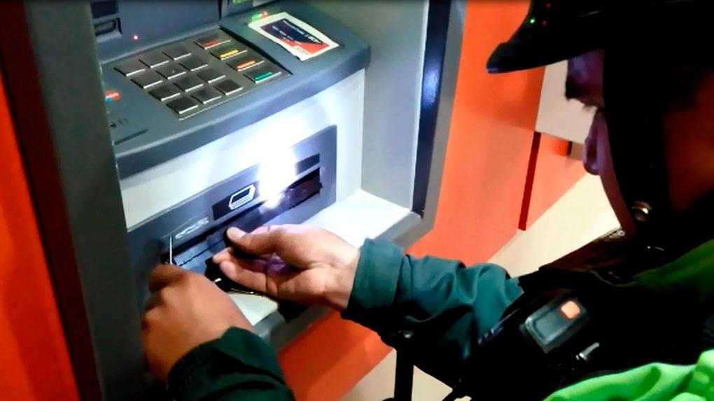 Un efectivo de la Policía retira las reglas del dispensador de billetes de uno de los cajeros.