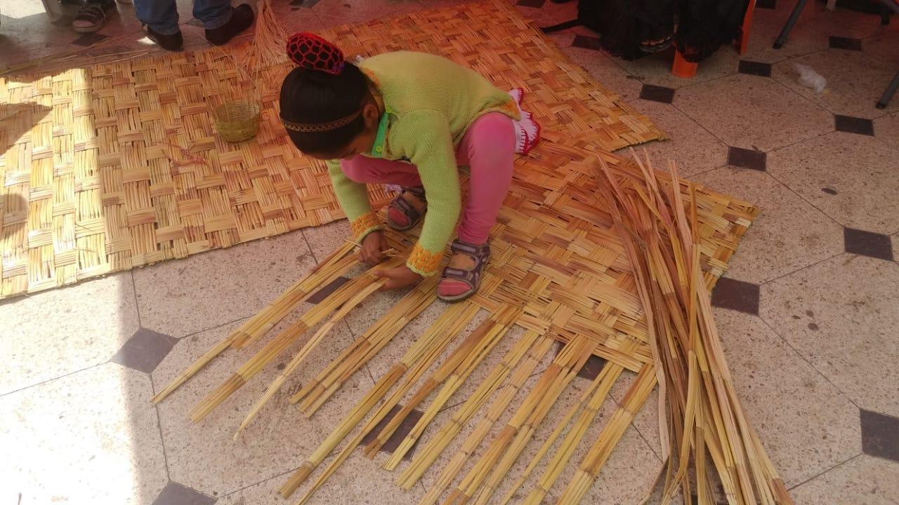 Niños aprender a elaborar esteras.