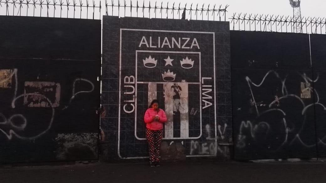 Vecina cuida el último escudo que queda al exterior del estadio de Alianza Lima.