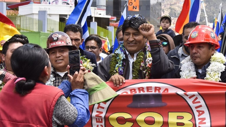 El presidente de Bolivia, Evo Morales, saluda a sus partidarios mientras marcha junto a miembros de organizaciones sociales, en La Paz.