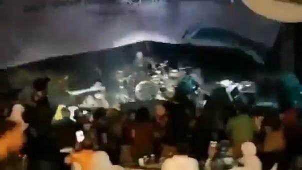 EL momento en que la ola destruye el escenario en el que tocaba la banda.