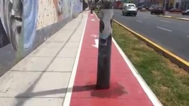 El ciclista avanza por la ciclovía de la avenida Argentina y se topa con los postes de luz, hasta con un teléfono público.