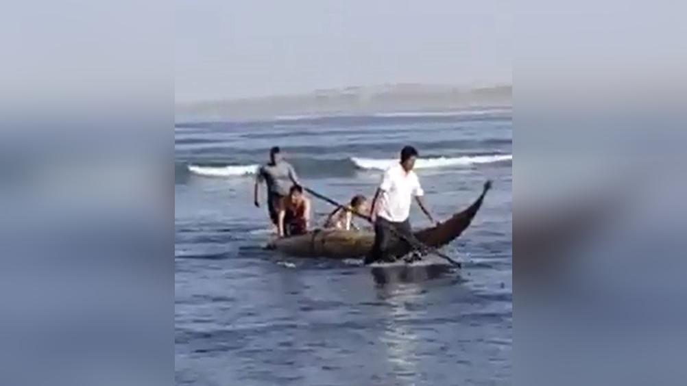 En el vídeo publicado en las redes sociales se aprecia al agente de la Policía Nacional con el uniforme de su institución y empujando el caballito de totorta donde fueron rescatados.