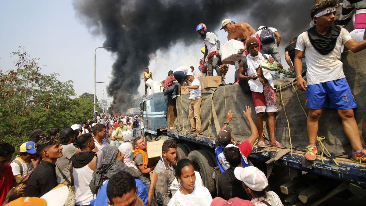 Gente intenta salvar la carga de ayuda humanitaria que fue quemada cuando se intentaba hacerla ingresar a Venezuela