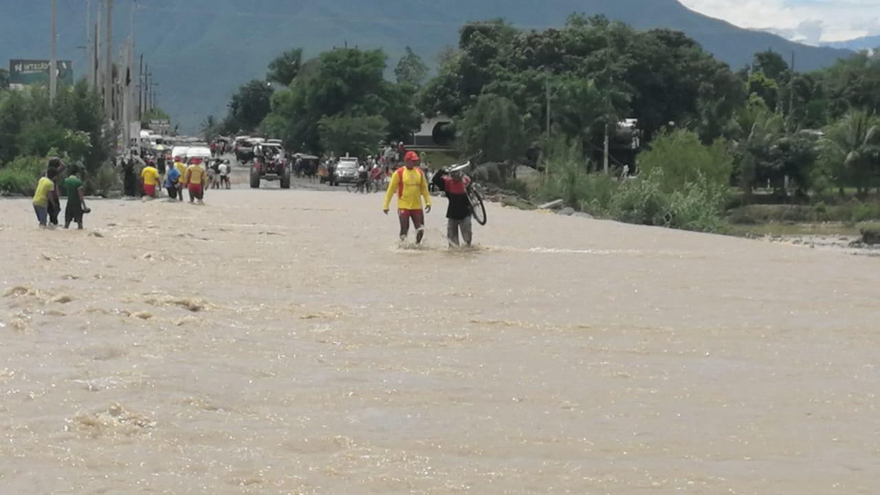 Salvavidas ayudan a cruzar a la población