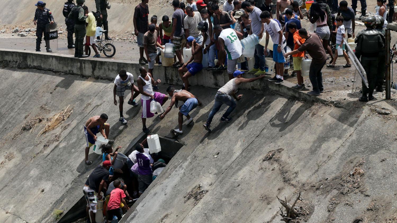 En una medida desesperada, un grupo de personas bajó al canal del contaminado ríoGuaire, en Caracas, para surtirse del líquido en una bocatoma ubicada a un costado. Fueron desalojadas por militares.