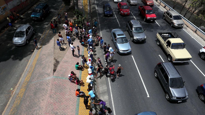 Personas tratando de recoger agua del río Guaire en la autopista Francisco Fajardo, en Caracas (Venezuela). El apagón que sufre el país desde hace varios días no permite la llegada de agua potable a las casas de varias regiones.