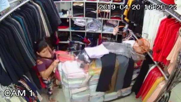 La mujer se llevó una pesada bolsa llena de ropa en un stand que vende trajes.