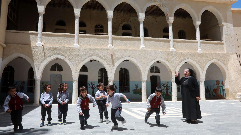 En una sala con dibujos colgados en las paredes, los niños de cinco a seis años recitan poemas en arameo.