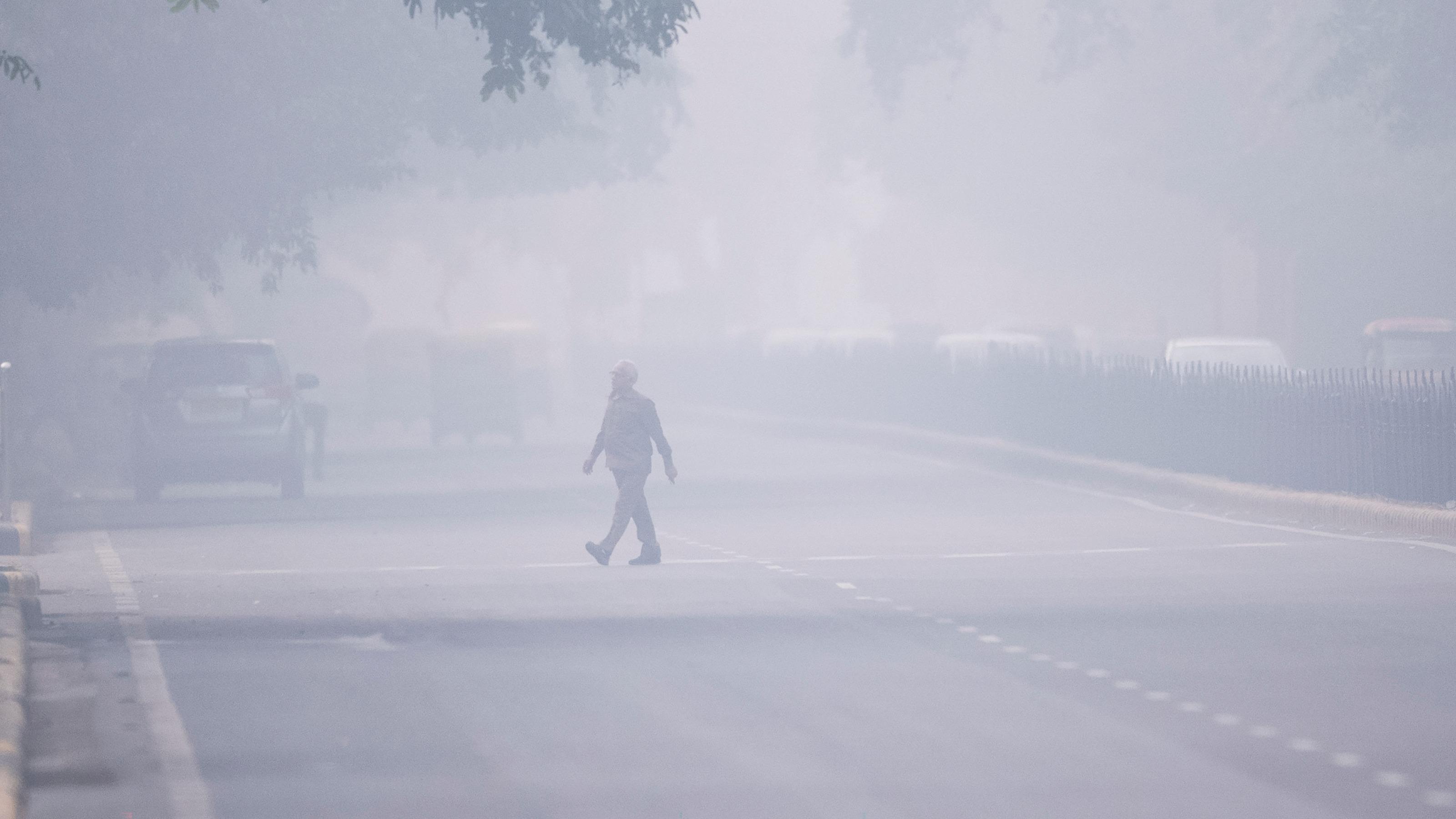 Un hombre camina en medio del smog en Nueva Delhi