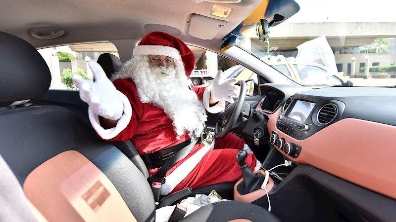 Armando grita con alegría a transeúntes una ¡feliz Navidad! a bordo de su auto, al que ha apodado 'Rodolfo'.