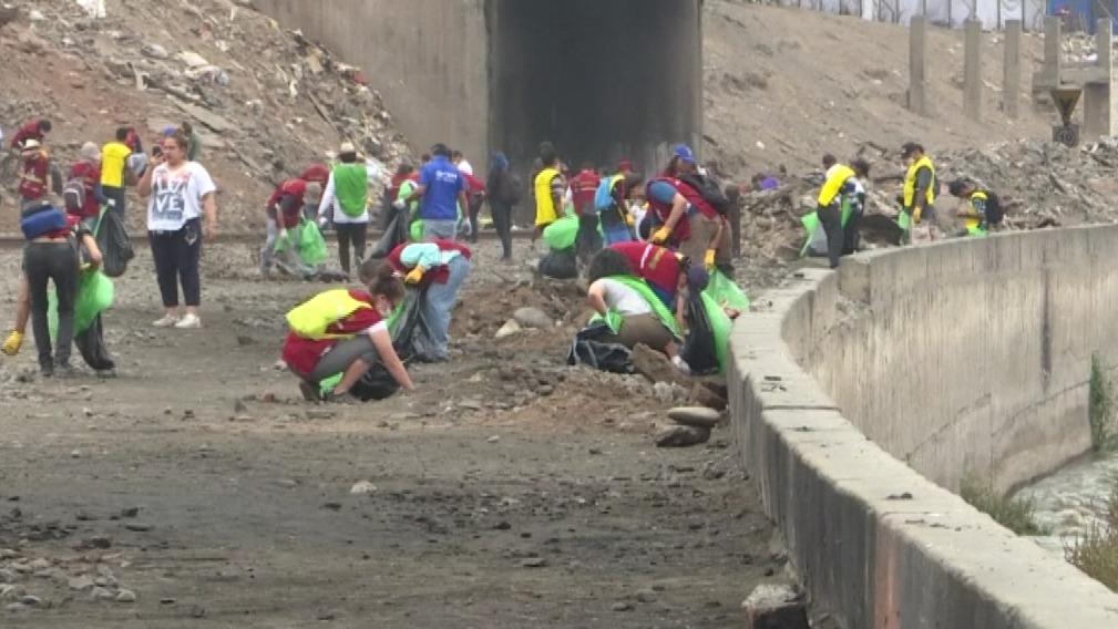 Con guantes, máscaras y grandes bolsas los ciudadanos venezolanos y peruanos recogieron plásticos, botellas y neumáticos del río Rímac.