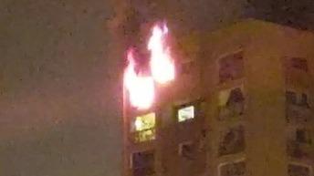 El fuego consume el último piso del edificio de departamentos.