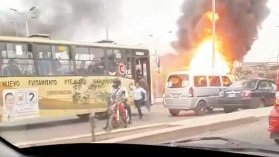 En este video se observa a pasajeros bajando rápidamente de un bus al ver el incendio del camión cisterna con gas.