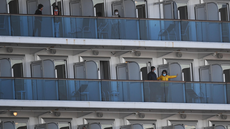 Varios pasajeros del crucero Diamond Princess permanecen en los balcones de sus cabinas de la nave anclada en Yokohama.