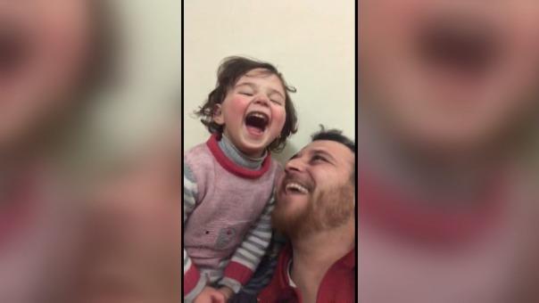 Salwa está de pie en el regazo de su padre en el salón. Su risa sincera es provocada por el estruendo siniestro de una bomba lanzada por un avión.
