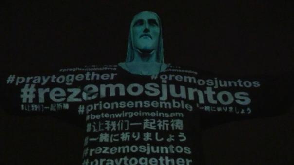 Proyección especial de las banderas sobre la estatua de hormigón de 30 metros de altura de Cristo con los brazos abiertos.