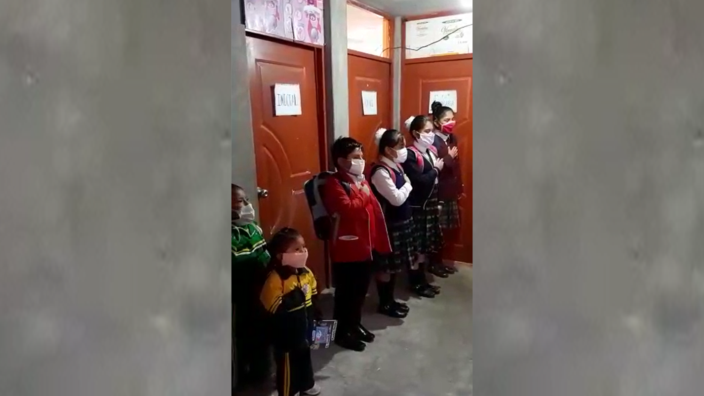 Los escolares se pusieron sus mascarillas para participar de la ceremonia, en el segundo piso de su casa.