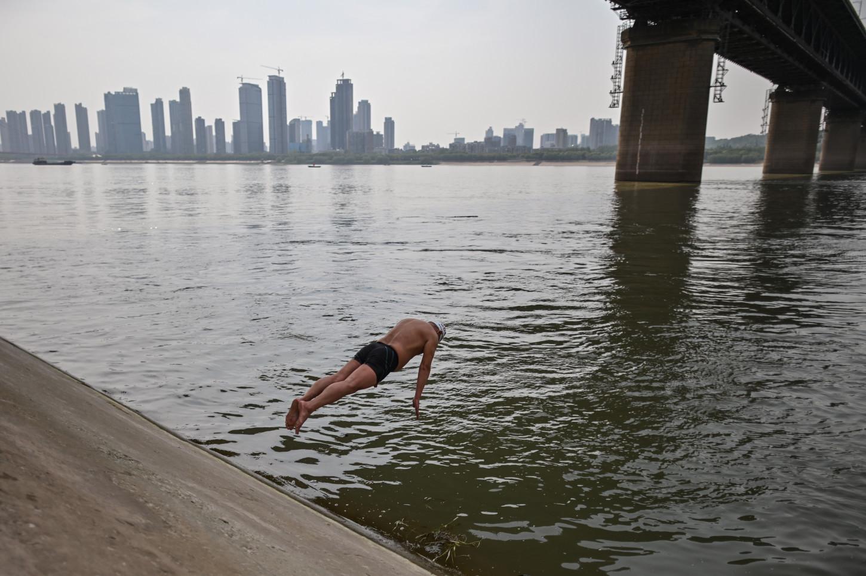 Más abajo, valientes nadadores se adentran en el río más largo de Asia, pese a la fría temperatura.