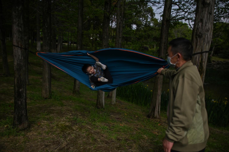 En un parque cercano, un abuelo acuna a su nieto tumbado en una hamaca. Al lado, varias familias con tiendas y manteles de pícnic disfrutan del sol.