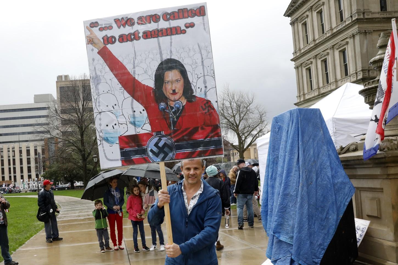 Se podía ver a más manifestantes afuera con carteles, incluido uno que representaba a la gobernadora Gretchen Whitmer como el dictador nazi Adolf Hitler.