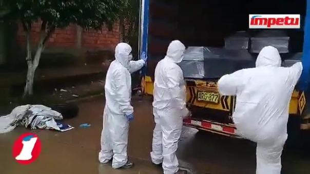 Equipo de recojo de cadáveres suben los cajones en los camiones con los protocolos respectivos.