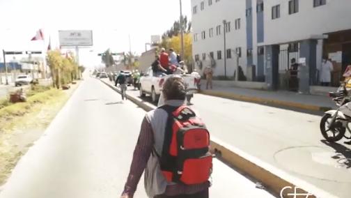 Mujer corre para intentar alcanzar el vehículo en el que se trasladaba el presidente Martín Vizcarra, mientras la caravana la sobrepasa.