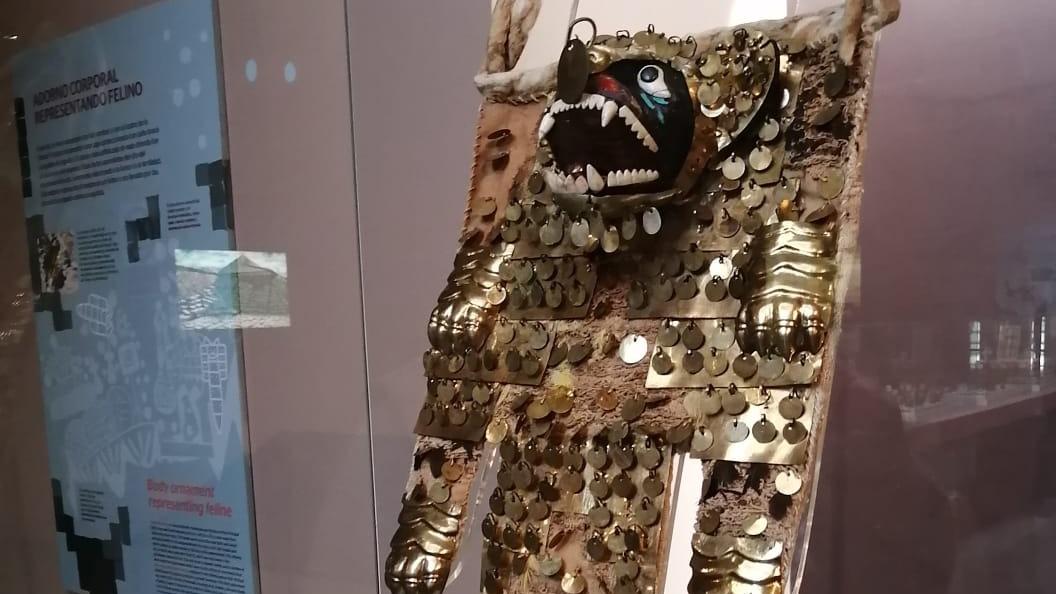 Dorsal que muestra la deidad felina que armoniza el metal, el algodón, plumas de aves tropicales y conchas, que resaltan la ferocidad del felino. Ubicación: Museo Santiago Uceda Castillo de Huacas de Moche.