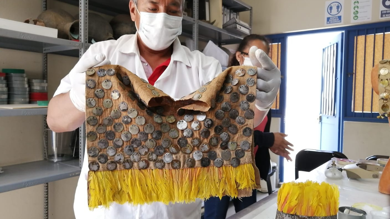 Vestimenta fúnebre elaborado con plata, algodón y plumas de ave tropical. Tras su restauración será digitalizada y posiblemente expuesta al público.