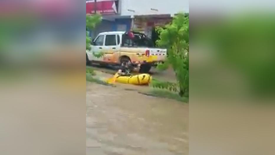 Un ciudadano captó a un hombre que subido en su pequeña embarcación trataba de avanzar en un canal colector que colapsó por la fuerte lluvia.
