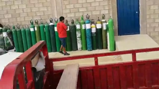 Familiares de pacientes con la COVID-19 forman largas filas en el exterior de una planta de oxígeno ubicada en la carretera Piura - Paita para poder recargar sus balones.