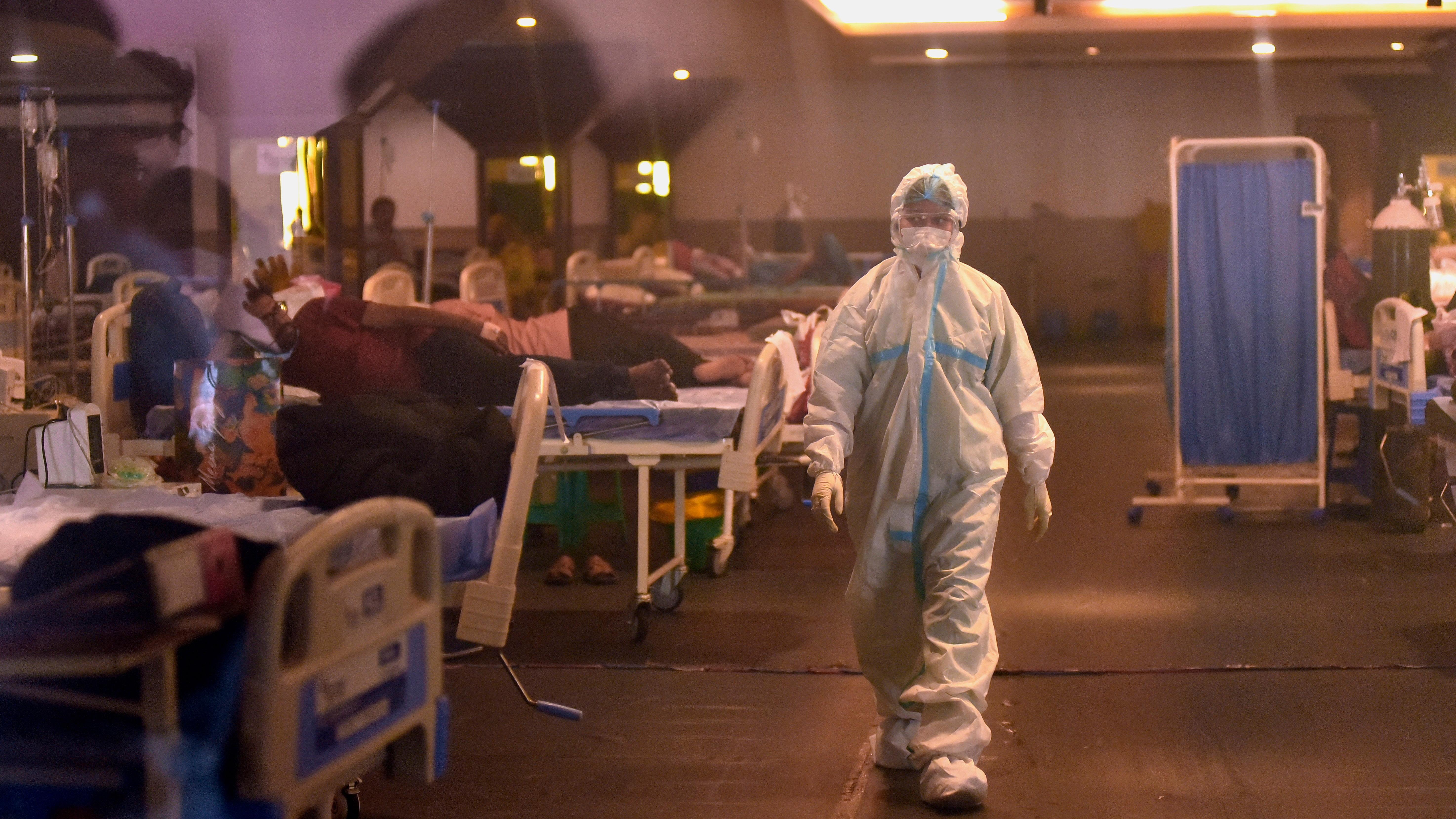 Un médico indio con equipo de protección personal (EPP) camina después de examinar a los pacientes dentro de un centro de atención COVID-19 y una sala de aislamiento cerca de un hospital en Nueva Delhi, India.
