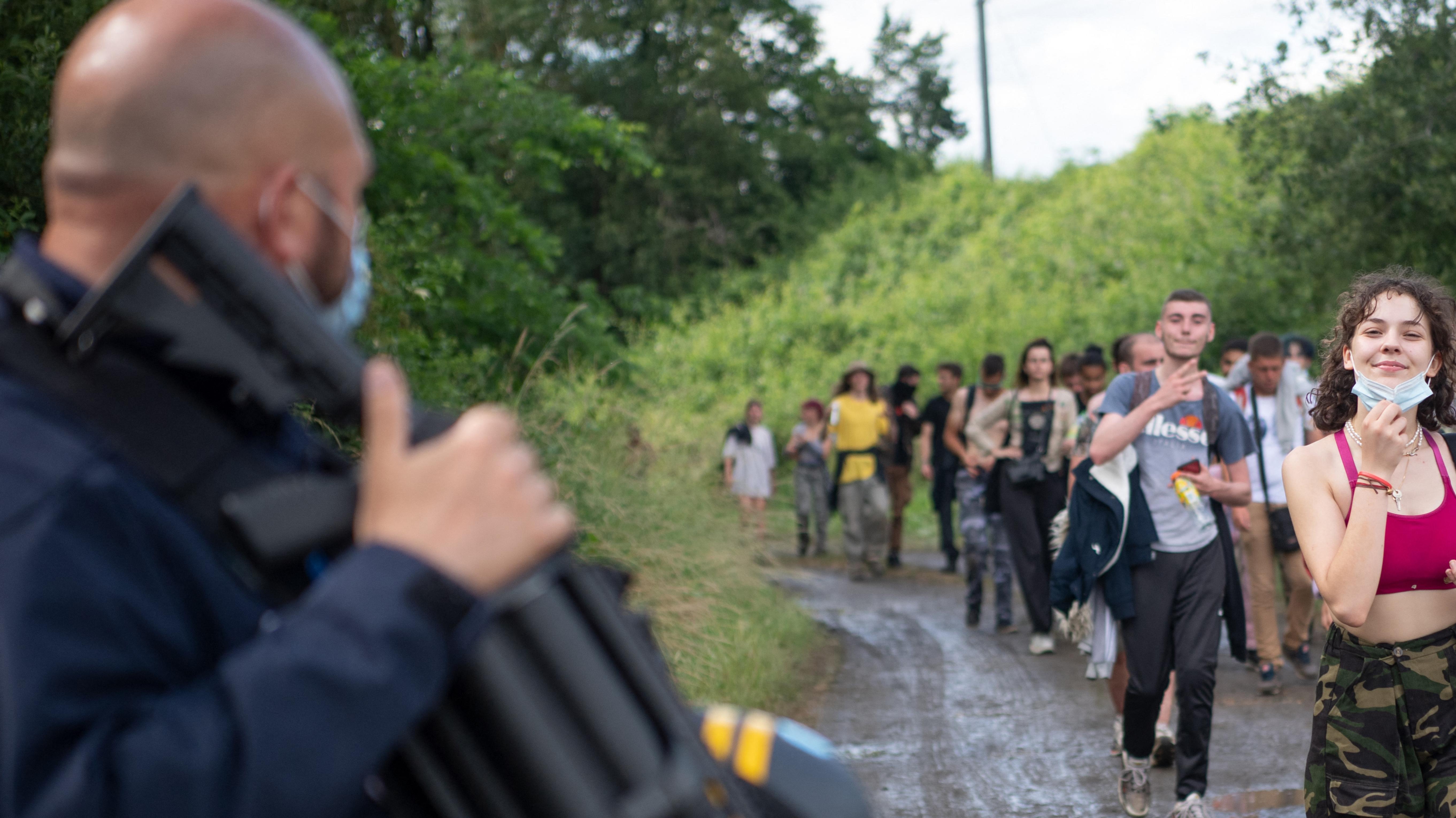Agentes de policía evacuan a los asistentes a la fiesta después de una fiesta rave ilegal en un campo en Redon, noroeste de Francia.