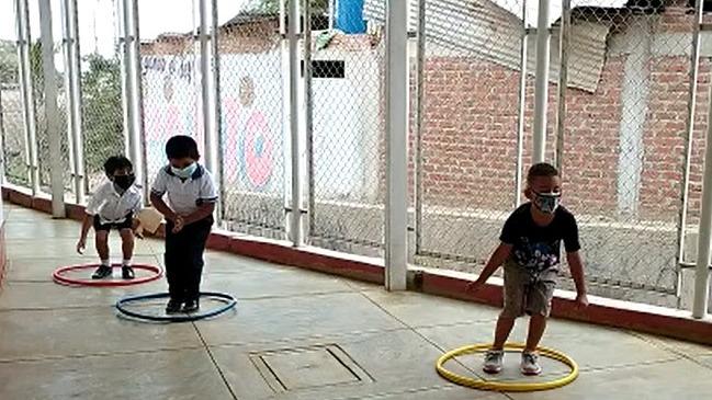Los pequeños escolares realizan juegos en el patio del colegio.